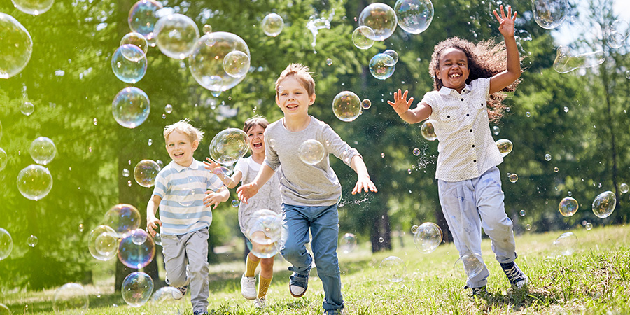 Four small children running through a field chasing bubbles
